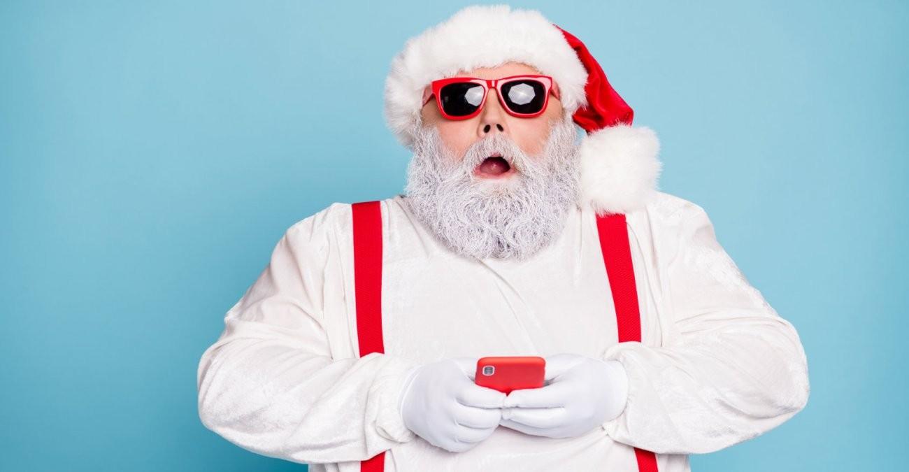 Ein Weihnachtsmann mit Smartphone ist erstaunt über den Einfluss sozialer Medien auf Weihnachten.