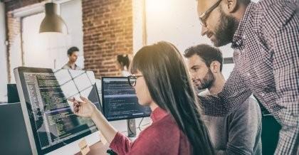 Drei Mitarbeiter*innen einer Software Agentur entwickeln eine ERP Software im Kundenauftrag und schauen sich gemeinsam den Code am Bildschirm an.