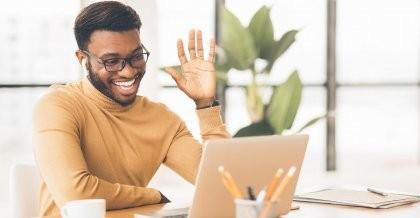 Ein Mitarbeiter sitzt an seinem Laptop und begrüßt winkend seine Kollegen in der Videokonferenz