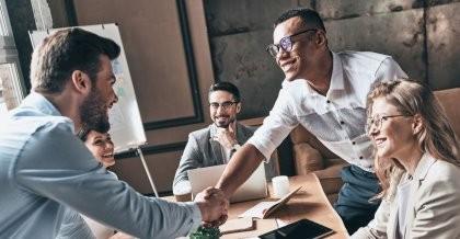 Ein Mitarbeiter eines Unternehmens, welches ein CRM System hat, schlägt mit einem Kunden auf eine gute Zusammenarbeit ein.