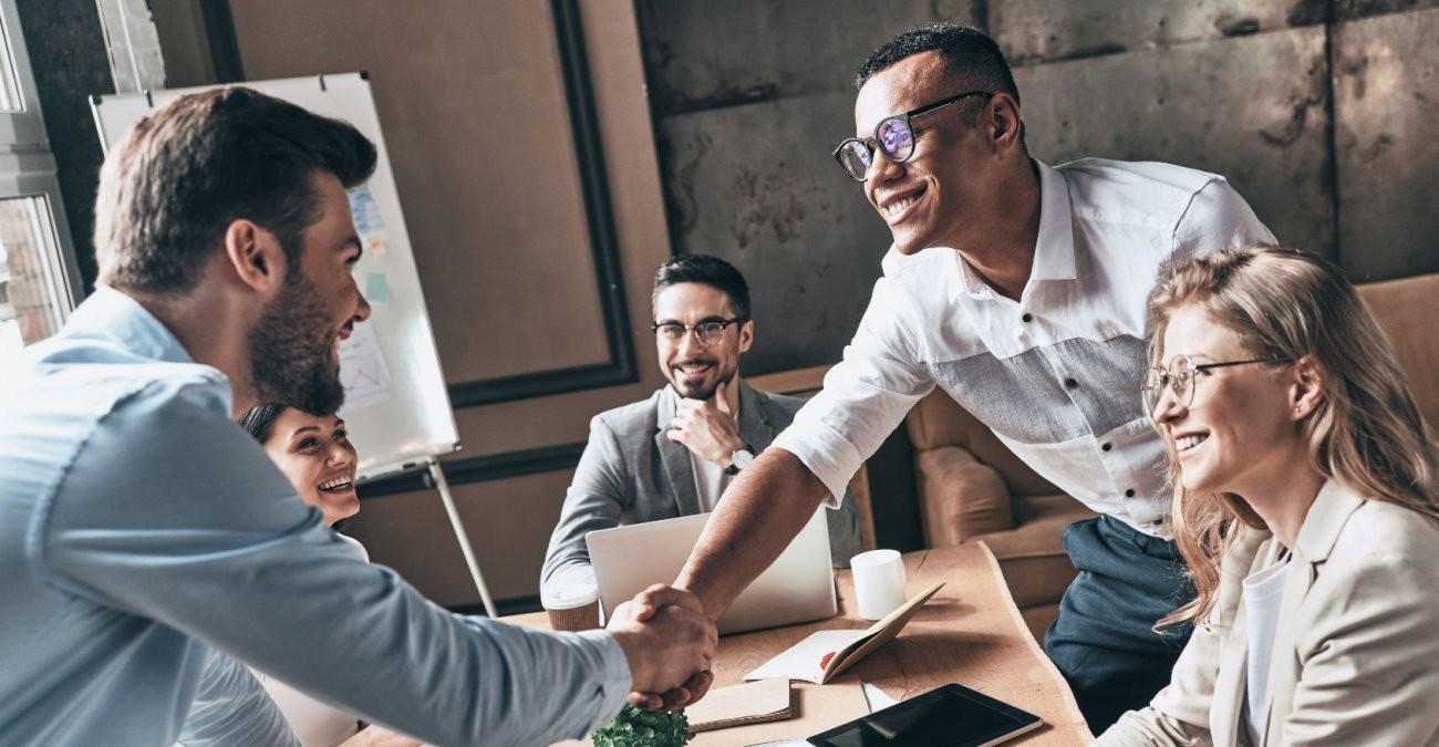 Ein Mitarbeiter eines Unternehmens schlägt mit einem Kunden auf eine gute Zusammenarbeit ein.