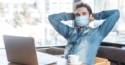 Ein Mitarbeiter einer Agentur sitzt mit Maske in einem Café an seinem Laptop.