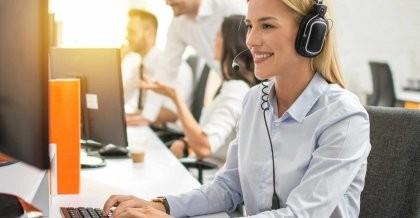 Eine Webentwicklerin mit Headset sitzt an ihrem Arbeitsplatz und nimmt die Probleme und Bugs einer Website eines Kunden auf.