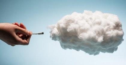 Sinnbildlich für die Cloud Native wird ein USB-Kabel von einer Hand eine Cloud gesteckt.