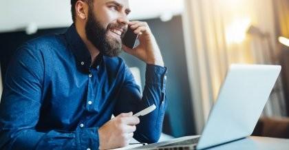 Ein PHP Entwickler sitzt am Computer und nimmt einen Anruf für eine PHP Notfallentwicklung entgegen.