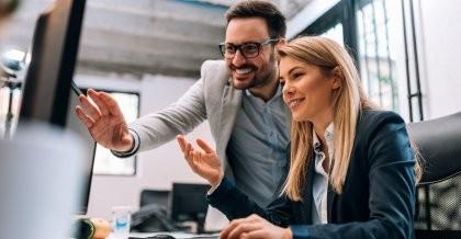 Zwei Mitarbeiter*innen von einem IT-Dienstleister erstellen eine Datenbank im Kundenauftrag und sehen gemeinsam auf einen Bildschirm.