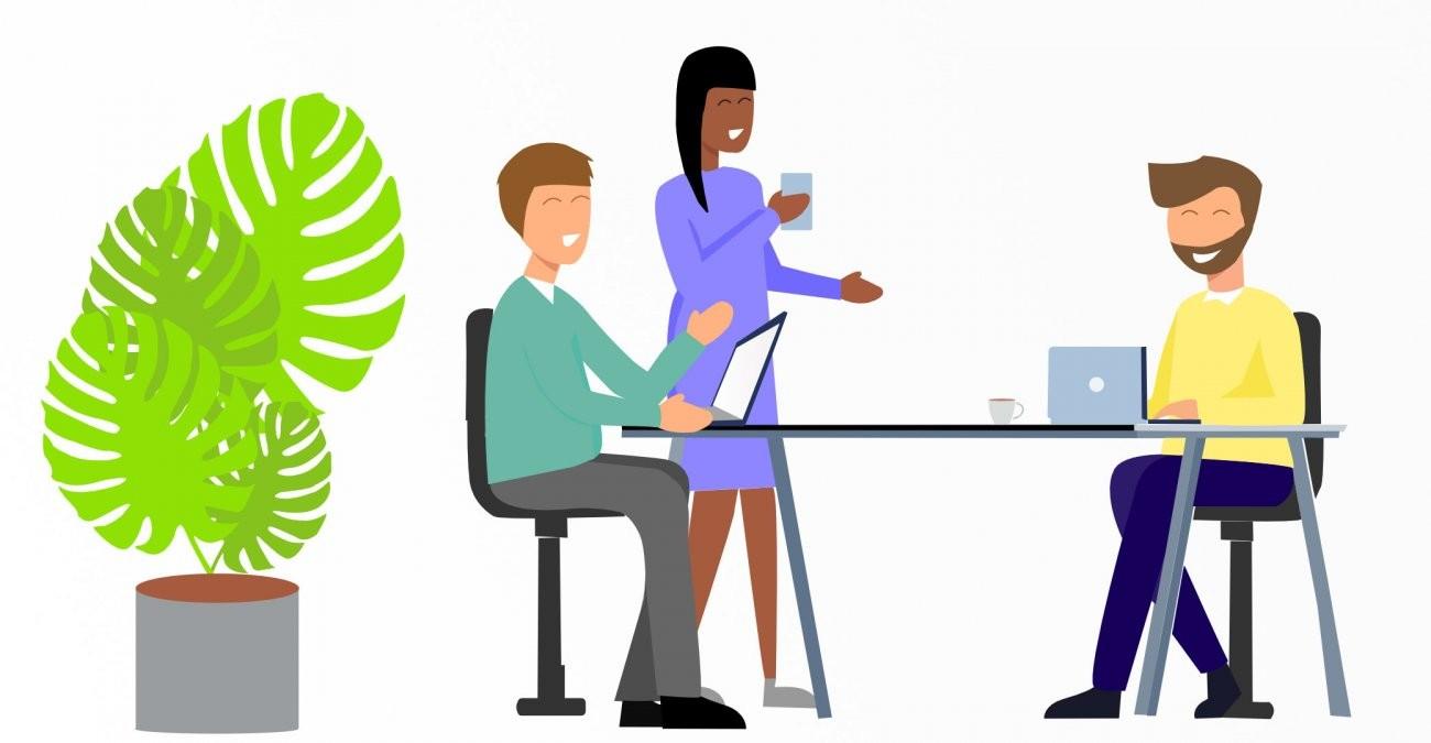 Drei Mitarbeiter*innen eines Unternehmens sitzen an ihrem Arbeitsplatz und tauschen sich über Digitalisierungsmaßnahmen aus.