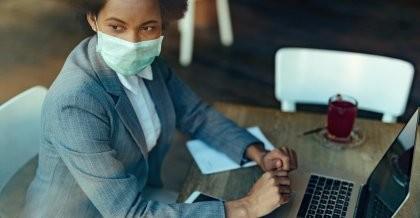 Eine Mitarbeiterin sitzt im Café und arbeitet mit Maske an ihrem Laptop.