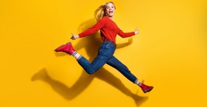 Eine fröhliche Frau springt vor einem gelben Hintergrund in die Luft und läuft nach rechts.
