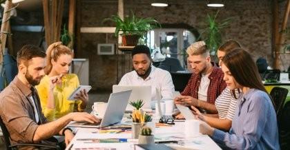 Ein junges Team arbeitet an einem großen Tisch mit Laptops und Unterlagen.
