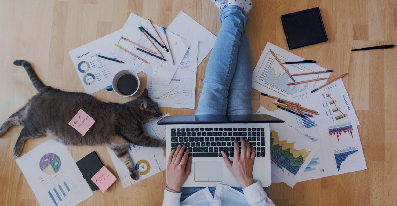 Ein junger Mitarbeiter einer Agentur sitzt auf dem Boden von Zetteln, Kaffee und einer Katze umgeben und arbeitet mit seinem Laptop auf dem Schoß.