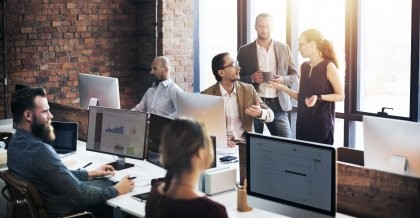 Ein Team sitzt im Büro an Rechnern und arbeitet mit der Intranet Software.