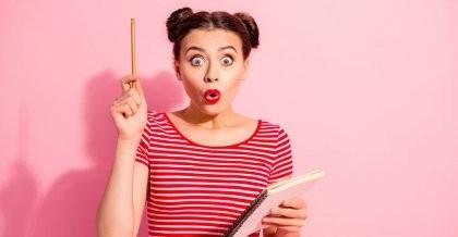 Eine junge Frau hat eine Idee, hält einen Notizblock in der Hand und einen Stift in die Höhe.