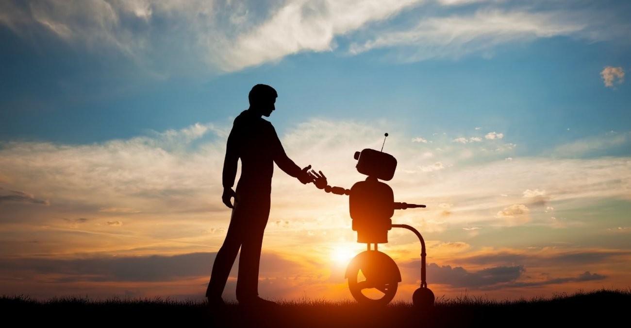 Ein Mensch gibt einem Roboter vor einem Sonnenuntergang die Hand.