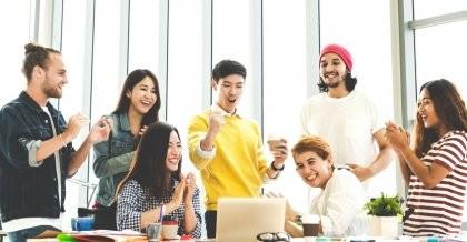 Ein junges Team schaut gemeinsam auf einen Laptop und feiert die erfolgreiche Beendigung des Sprints.