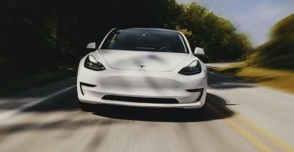 Ein Tesla Auto fährt mit hoher Geschwindigkeit die Straße entlang Richtung Kamera.