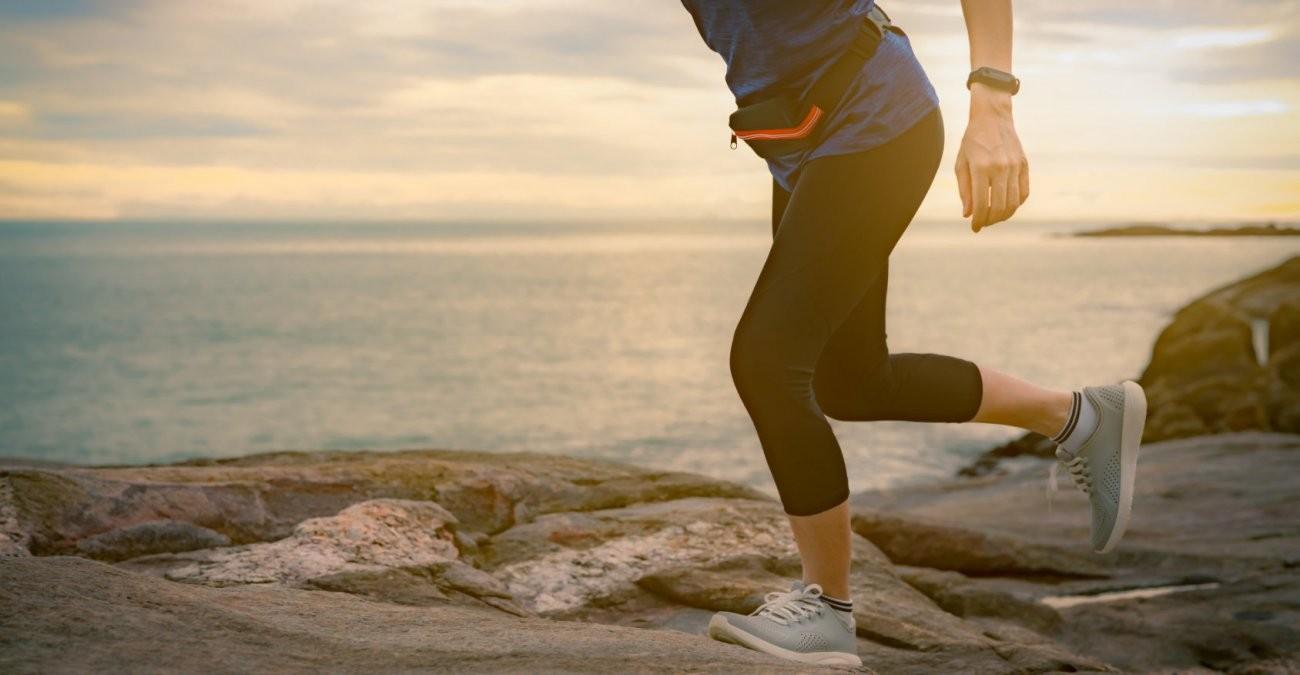 Eine Frau läuft in Turnschuhen und Laufkleidung einen Weg am Meer bei Sonnenuntergang entlang