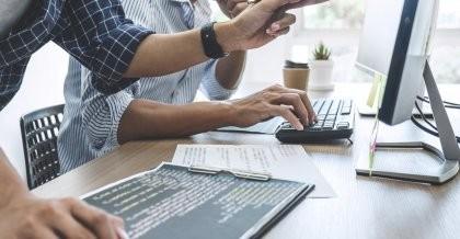 zwei Personen sitzen am Schreibtisch und arbeiten mit dem Computer