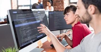 Zwei Menschen programmieren zusammen an einem PC