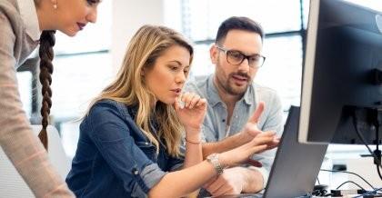 Zwei Frauen und ein Mann arbeiten zusammen an einem Computer
