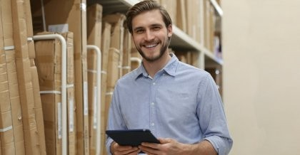 Mann führt Inventarliste mit einem Tablet vor einem Regal
