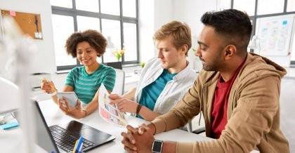 Drei Kollegen sitzen in einem hellen Büro vor einem Laptop