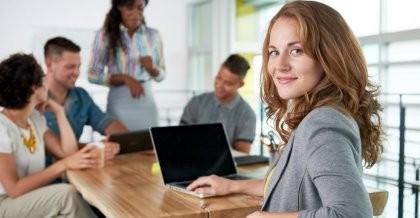 Frau sitzt mit dem Kollegium am Schreibtisch
