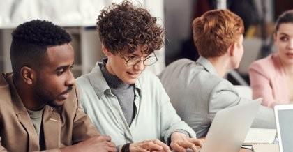 Zwei Menschen sitzen im Büro an einem Laptop