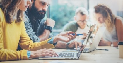 Zwei Mitarbeiter*innen einer Internetagentur planen die Kommunikation mit ihren Kunden am Laptop und mit Zettel und Stift.
