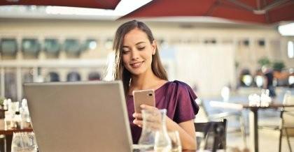 Frau sitzt im Café mit Laptop und Handy