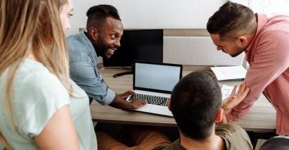 Vier Leute arbeiten gemeinsam am PC