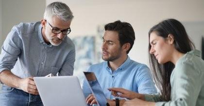 Drei Arbeitskollegen sitzen vor einem Laptop im Büro