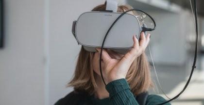 Frau im grünen Pulli schaut in eine graue Virtual Reality Brille