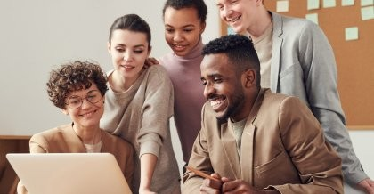 Fünf Menschen sitzen und stehen vor einem Schreibtisch am PC