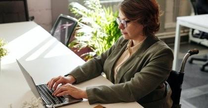 Frau im Rollstuhl sitzt am Schreibtisch vor einem Laptop