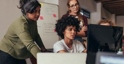 Teammitglieder einer Software Agentur besprechen die nächsten Schritte der Softwareentwicklung an ihrem Arbeitsplatz und zeigen auf einen Computerbildschirm.