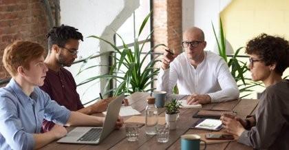 Menschen sitzen zusammen an einem Schreibtisch und haben Laptops und Tablets dabei und diskutieren
