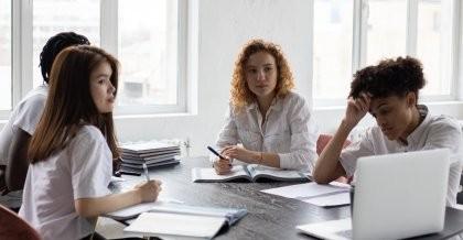 Vier Frauen sitzen am Tisch und schauen auf einen Bildschirm