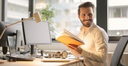 Mann sitzt am Schreibtisch am PC