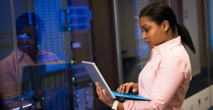 Frau hält einen Laptop in der Hand und überprüft Rechner