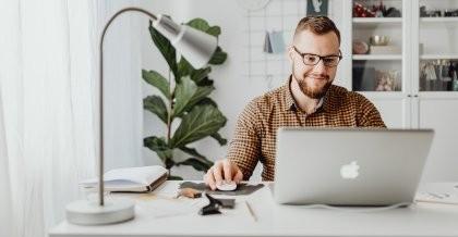Mensch sitzt am Schreibtisch und arbeitet mit einem Laptop