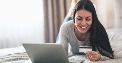 Eine Frau liegt mit ihrem Laptop auf dem Bett und benutzt einen Onlineshop mit ihrer Kreditkarte.
