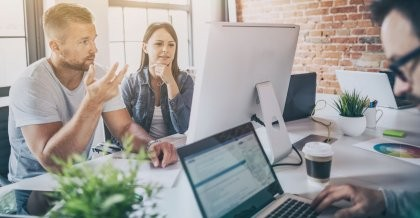 Mitarbeiter*innen einer Internetagentur schauen auf einen Bildschirm und besprechen das responsive Webdesign ihres aktuellen Kundenprojekts.