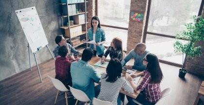 Eine Agentur bespricht das Konzept für das Monitoring für ihre Kunden in einem Meeting-Raum an einem Tisch mit Flipchart.