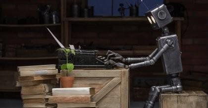 Sinnbildlich für die Industrie 4.0 sitzt ein blecherner Roboter an einer Schreibmaschine.