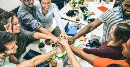 Junge Gründer*innen eines Start-ups stehen im Kreis und schlagen auf ihren Code for Equity Vertrag ein.