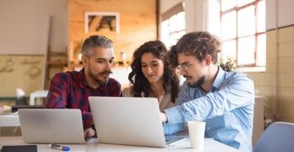 Drei Mitarbeiter*innen planen den Einsatz vom Internet der Dinge im Unternehmen an einem Laptop.