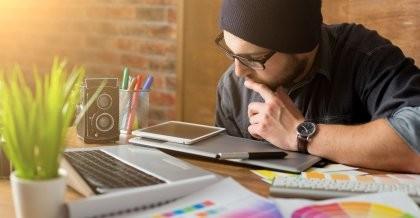 Ein Entwickler schaut sich eine Website auf einem Tablet an und optimiert diese im Rahmen eines Website Relaunches.