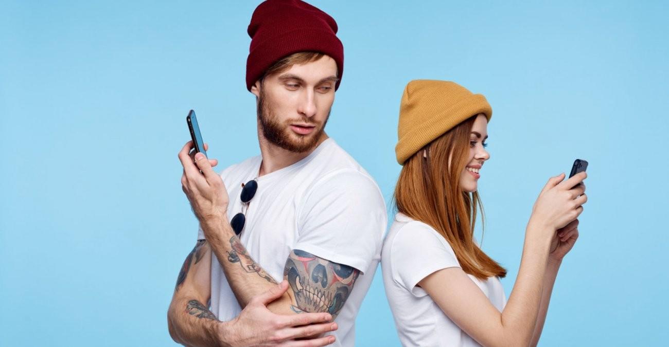 Ein junges Paar steht Rücken an Rücken, sie ist in ihr Smartphone vertieft, er schaut misstrauisch über die Schulter zu ihr. Automatisiert Technologie das Liebesleben?