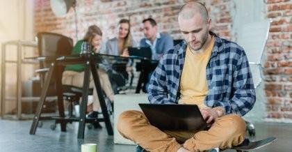 Ein Entwickler sitzt auf einem Skateboard und benutzt an seinem Laptop Laravel für die Erstellung einer responsive Website.